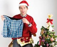 Человек развертывая подарок рождества Стоковые Изображения