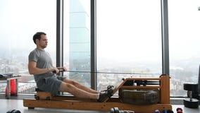 Человек разрабатывая на машине rowing на спортзале видеоматериал