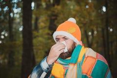 Человек разработать после того как он больной дуя нос и чихать, кашляющ Зараженный человек дуя его нос в салфетке из-за стоковые изображения rf
