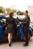 Человек раскрывает автомобильную дверь для женщины стоковое фото rf
