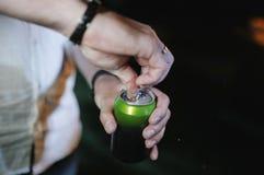 Человек раскрывает консервную банку с его рукой в конце-вверх стоковое изображение