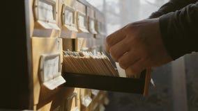 Человек раскрывает ящик базы данных Молодой библиотекарь раскрывает индекс карты библиотеки Архив, база данных, концепция библиот сток-видео