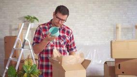 Человек распаковывает коробку блюд во время движения и находит повреждение сток-видео