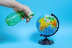 Человек распыляет глобус от зеленой бутылки стоковое изображение rf