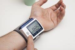 Человек рассматривает кровяное давление давление preasure монитора макроса крови цифровое высокое изолированное стоковая фотография rf