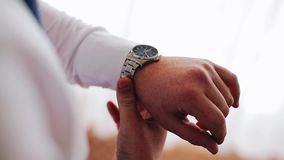 Человек регулирует его дозор на его руке Славный конец-вверх видеоматериал