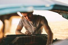 Человек ремонтируя его автомобиль на шоссе Стоковая Фотография