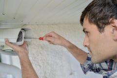 Человек ремонтируя камеру слежения Стоковые Фотографии RF