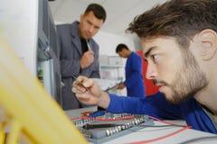 Человек ремонтируя принтер на работе стоковое фото rf