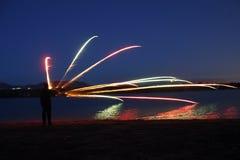 Человек рисуя радугу в небе стоковое фото