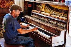 Человек рояля внутри городской гостиницы в городе Dawson, Юконе стоковая фотография