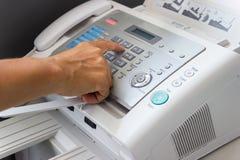 Человек руки использует факс в офисе стоковая фотография