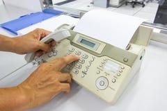 Человек руки использует факс для отправки бумаги в офисе стоковое фото