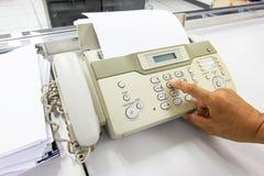Человек руки использует факс для отправки бумаги в офисе стоковое фото rf