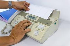 Человек руки использует факс для отправки бумаги стоковое фото rf