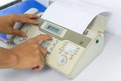 Человек руки использует факс для отправки бумаги стоковое фото