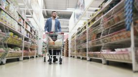 Человек свертывает вагонетку с едой beetwen полки и выбирает продукты в супермаркете, снятом steadicam акции видеоматериалы