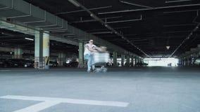 Человек свертывает девушку в вагонетке от супермаркета в круге в подземной стоянке видеоматериал