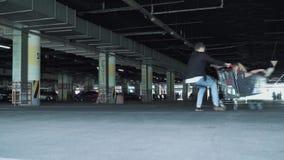 Человек свертывает девушку в вагонетке от супермаркета в подземной стоянке акции видеоматериалы