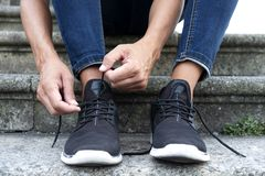 Человек связывая или развязывая шнурки его тапок стоковое изображение rf
