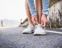 Человек связывая пакостные ботинки на дороге стоковое изображение rf