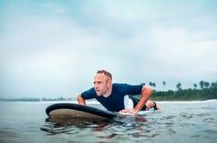 Человек серфера плавает на доску прибоя, ждет волны Стоковое Изображение RF