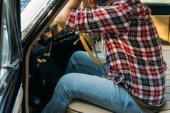 Человек сидит за рулем, водитель взгляд из заднего окна Вид сзади туристского парня в автомобиле Перемещение и лето стоковая фотография