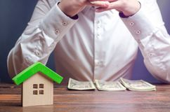 Человек сидит мысль над сортированными деньгами Планирование расхода и финансовые вопросы Вычисление налога на собственность, опл стоковые фотографии rf