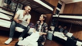 Человек сидит на кровати смотря карту и девушка распаковывает сумку стоковое изображение rf