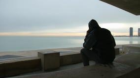 Человек сидит на стенде говоря на телефоне и смотря море сток-видео