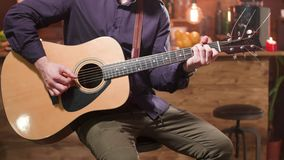 Человек сидит на стуле высокой планки и играет акустическую гитару сток-видео