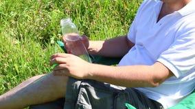 Человек сидит на стуле пикника в освещенном луге Он отдыхает, выпивает воду от бутылки и закрывает его Взмах трав и цветков для сток-видео