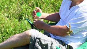Человек сидит на стуле пикника в освещенном луге Он отдыхает, закрывает бутылку воды, и переносит его ногу Взмах f трав и цветков видеоматериал