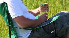 Человек сидит на стуле пикника в освещенном луге Он принимает остатки, закрывает бутылку воды, кладет его в стойку и кладет его р видеоматериал