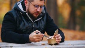 Человек сидит на таблице и еде законсервированного потушенного мяса используя нож конец вверх сток-видео