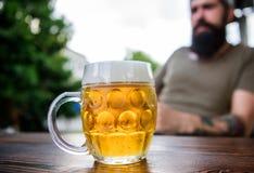 Человек сидит терраса кафа наслаждаясь пивом defocused Концепция алкоголя и бара Творческий молодой винодел Пиво ремесла молодо,  стоковая фотография rf