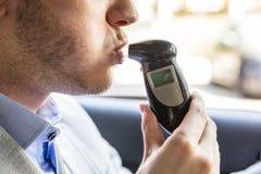 Человек сидя внутри автомобиля принимая тест на алкоголь стоковые фото