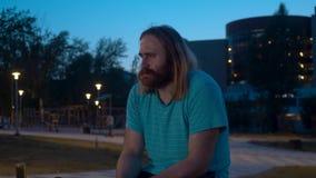 Человек сидя в парке и усмехаться акции видеоматериалы