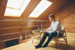 Человек сидя дома и работая на компьтер-книжке мужчина работая от домашнего офиса просторной квартиры Стоковое Фото