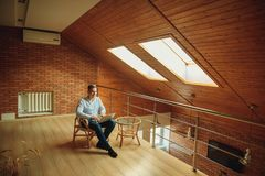 Человек сидя дома и работая на компьтер-книжке мужчина работая от домашнего офиса просторной квартиры Стоковая Фотография RF