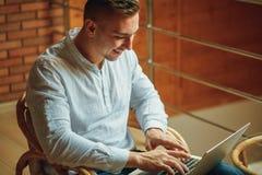 Человек сидя дома и работая на компьтер-книжке мужчина работая от домашнего офиса просторной квартиры Стоковая Фотография