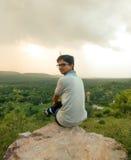 Человек сидя на верхней части горы Стоковое Изображение