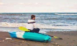 Человек сидя на пляже каяка на море Стоковые Изображения