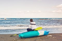 Человек сидя на пляже каяка на море Стоковые Фотографии RF