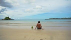 Человек сидя на пляже Стоковые Фото