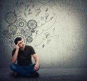 Человек сидя на поле крепко думая, находит решение для того чтобы разрешить проблему Различное воображение, альтернативная идея М стоковое изображение