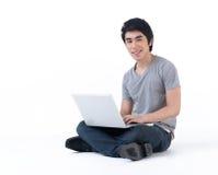 Человек сидя на поле, работа с компьтер-книжкой стоковое изображение