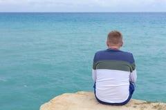 Человек сидя на скале Турист ovelooking открытое море Волны shoaling и approcahing морское дно Расслабляющее тропическое назначен стоковое фото