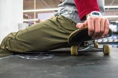 Человек сидя на скейтборде стоковое изображение rf