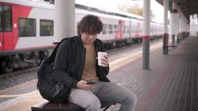Человек сидя на стенде и сеть занимаясь серфингом на железнодорожном вокзале сток-видео